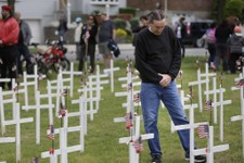 -                Joe Schulmann pauses in prayer over a cross bearing the name of his neighbor, Michael Wick, who was killed during the Vietnam War, at the College Point Memorial Day Parade in New York,