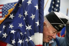 -                Korean War veteran Bob Pellow, 84, a flag bearer, puts his hat back on after strong winds knocked it off during Memorial Day ceremonies at the State Veterans Cemetery in Little Falls, M