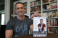"-                In this photo taken on May 22, 2013, author Dan Savage holds his new book, ""American Savage,"" as he sits in his home in Seattle. Savage's latest book, ""American Savage,"" was released on"