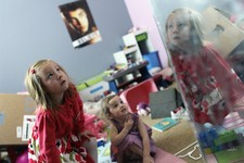-                With her face reflected in a mirror, Coy Mathis, left, a transgender girl, plays with her sister, Auri, 2, center, at their home in Fountain, Colo., on Monday, Feb. 25, 2013. Coy's pare