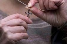 -                Shirley Chaplin poses for photographs while holding her crucifix necklace before a press conference in London, Tuesday, Jan. 15, 2013.  Europe's highest court ruled Tuesday against Shir