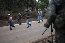 -                In this May 2, 2013 photo, residents walk past a cordon of soldiers standing guard at a checkpoint in San Rafael Las Flores, Guatemala. The soldiers and the fear bring back memories of