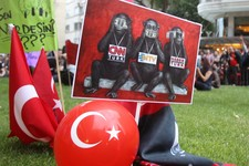 -                In this Sunday, June 2, 2013 photo protesters display a banner depicting Turkish media as the three wise monkeys who see no evil, speak no evil and hear no evil, outside Haber Turk tele