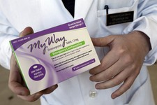 -                FILE - In this May 2, 2013 photo, pharmacist Simon Gorelikov holds a generic emergency contraceptive, also called the morning-after pill, at the Health First Pharmacy in Boston. A feder