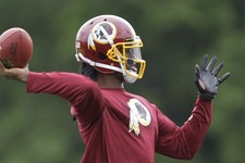 -                Washington Redskins quarterback Robert Griffin III throws a pass during team practice at Redskins Park, Thursday, June 6, 2013, in Ashburn, Va. (AP Photo/Luis M. Alvarez)
