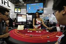 -                In this photo taken on Thursday, May 23, 2013, an attendant demonstrates the game of baccarat on a baccarat gaming table during the Global Gaming Expo Asia in Macau. Almost all of Macau