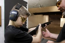 -                In this Sunday, May 19, 2013, photo, Dan Blackford, right, shows Rory Strain, 12, how to hold a shotgun at a shooting range Sunday, May 19, 2013, in Houston. Strain lives in the northwe