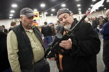 -                FILE - In a Saturday, Jan. 5, 2013 file photo, gun owners discuss a potential sale of an AR-15, during the 2013 Rocky Mountain Gun Show at the South Towne Expo Center in Sandy, Utah. Ne