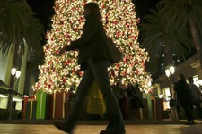 -                In this Thursday, Dec. 20, 2012, photo, a holiday shopper walks past a large Christmas tree at Fashion Island shopping center in Newport Beach, Calif. Holiday shopping, strong auto sale