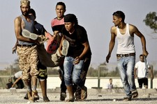 -                In this Saturday, June 8, 2013 photo, Libyans help a wounded man during fighting outside the office of the Libya Shield pro-government militia in Benghazi, Libya. The violence which lef