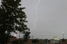 -                Lightning flashes near Wauconda, Ill. High School Wednesday, June 12, 2013 evening as storms roll into the Suburbs of Chicago. A massive line of storms packing hail, lightning and tree-