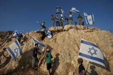 -                File - In this Sept. 20, 2011file photo, Israeli settler youths wave Israeli flags at the start of a protest march against Palestinian statehood, from the West Bank Jewish settlement of