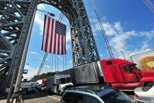 -                In this photo provided by the Port Authority of New York and New Jersey, traffic passes under a large American flag that hangs from the superstructure of the George Washington Bridge in