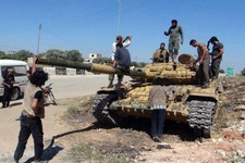 -                In this Friday, June 14, 2013 citizen journalism image provided by Edlib News Network, ENN, Syrian rebels stand on top of a tank they took after storming the Iskan military base in Idli