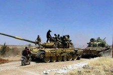 -                In this Friday, June 14, 2013 citizen journalism image provided by Edlib News Network, ENN, Syrian rebels gather on top of a tank they took after storming the Iskan military base in Idl