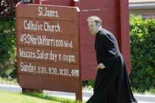 -                In this Sunday, June 16, 2013 photo, a clergyman walks up a small rise near the entrance of St. James Catholic Church in Ogden, Utah after police say Charles Richard Jennings Jr. walked