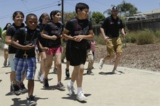 -                Schoolchildren from Chase Avenue Elementary run alongside NASCAR auto racing driver Jimmie Johnson, right, during visit to the school by the driver Tuesday, June 18, 2013, in El Cajon,
