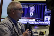 -                Fed Chairman Ben Bernanke is on a television screen as trader James Dresch works in a booth on the floor of the New York Stock Exchange Wednesday, June 19, 2013.  The Federal Reserve of