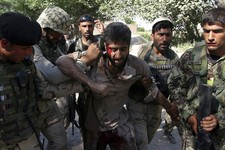 -                Afghan police carry an injured Taliban fighter, who was captured after an overnight clash with Afghan police in Jalalabad, in the eastern province of Nangrahar, east of Kabul, Afghanist