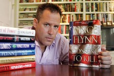 "-                FILE - In a Sept. 2, 2005 file photo, best-selling author Vince Flynn poses with the dust jacket of his new book, ""Consent to Kill,"" and copies of his six other books in his home in Edi"