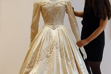 -                A Christie's employee adjusts Elizabeth Taylor's first wedding dress, designed by the legendary costume designer Helen Rose, at the auction house Christie's in London, Wednesday, June 1