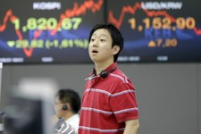 -                A currency trader asks a question to his colleague near a screen showing the Korea Composite Stock Price Index (KOSPI), left, and foreign exchange rate at the foreign exchange dealing r