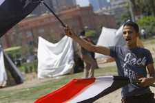 -                An Egyptian flag vendor waves flags in front of new erected strike tents in Tahrir Square, the focal point of Egyptian uprising in Cairo, Egypt, Saturday, June 22, 2013. Egypt's largest
