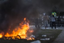 -                A man holds a brazilian flag near a burning barricade during a protest outside the Minerao stadium during a soccer Confederations Cup match between Japan and Mexico in Belo Horizonte, B