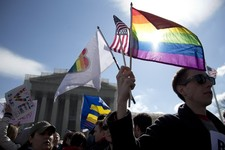 -                FILE - It is March 27, 2013, file photo Kevin Coyne of Washington holds flags in front of the Supreme Court in Washington as the court hears arguments on gay marriage. Sometime this ear