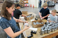 -                This Friday June 21, 2013 photo shows Kirsten Oschwald, left, and a group of her students volunteering by putting labels on canned food at the Roadrunner Food Bank in Albuquerque, N.M.