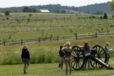 -                In this  June 5, 2013 file photo tourist gather near a Confederate artillery piece that sit atop a ridge above the field of Pickett's Charge, in Gettysburg, Pa.  As the 150th anniversar