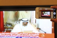 -                A man prepares to take a picture with his mobile photo of a televised address by Qatar's Emir Sheik  Hamad bin Khalifa Al Thani, in Doha, Qatar,Tuesday, June 25, 2013. Qatar's ruler sai