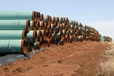 -                FILE - In this Wednesday, Feb. 1, 2012 file photo, miles of pipe ready to become part of the Keystone Pipeline are stacked in a field near Ripley, Okla. President Barack Obama says that