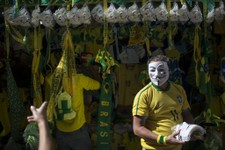 -                A vendor sells Guy Fawkes masks and Brazilian flags on the sidelines of a protest march moving toward the Mineirao stadium before a Confederations Cup semifinal soccer match between Bra