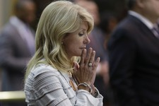 -                Sen. Wendy Davis, D-Fort Worth, reacts after she was called for a third and final violation in rules to end her filibuster attempt to kill an abortion bill, Tuesday, June 25, 2013, in A