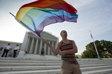 -                Gay rights advocate Vin Testa waves a rainbow flag in front of the Supreme Court at sun up in Washington, Wednesday, June 26, 2013. Justices are expected to hand down major rulings on t