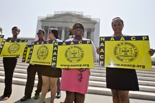 -                FILE - This June 25, 2013 file photo shows representatives from the NAACP Legal Defense Fund standing outside the Supreme Court in Washington awaiting a decision in Shelby County v. Hol