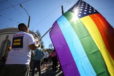 -                Larry Pascua carries a rainbow flag at a celebration for the U. S. Supreme Court's rulings on Prop. 8 and the Defense of Marriage Act in the Castro District in San Francisco, on Wednesd