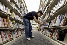 -                Timothy Ngo shelves books at the Barbara Bush Branch Library Friday, June 28, 2013, in Spring, Texas. The nation's librarians will be recruited to help people get signed up for insuranc