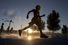 -                Five-year-old Ashawn Rabb runs through a fountain of water at the Red Ridge Park kids water park, Thursday, June 27, 2013 in Las Vegas.  Children with their parents stayed past sundown