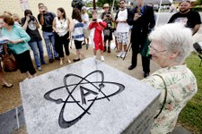 -                Gael Murphy, an Atheist, poses for a photo on the bench during the unveiling of an Atheist monument outside the Bradford County Courthouse on Saturday, June 29, 2013 in Stark, Fla.  The