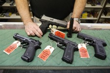 -                FILE - In this   Thursday, June 27, 2013, file photo Richard Taylor manager of at Firing-Line gun store in Aurora, Colo., shows some of the pistols that he won't be able to sell after J
