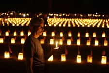 -                A member of the public holds a candle near luminaries that mark the graves of Union dead at Soldiers' National Cemetery during ongoing activities commemorating the 150th anniversary of