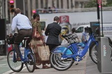 -                In this Tuesday, June 25, 2013, photo, a biker rides without a helmet on a Citibike, as part of New York City's bike sharing system, in New York.  Under Mayor Bloomberg, the city has cr