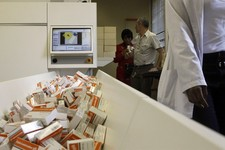 -                FILE - In this Nov. 15, 2012 file photo a newly mechanized pharmaceutical machine that helps pharmacists dispense medicine is loaded with ARV medication, at the U.S. sponsored Themba Le