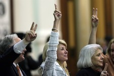 "-                FILE -  In this Tuesday, June 25, 2013, file photo, Sen. Wendy Davis, D-Fort Worth, center, holds up two fingers to signal a ""No"" vote as the session where tshe tried to filibuster an a"