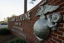 -                FILE -This Dec. 2, 2005 file photo shows cars entering the main gate at Camp Lejeune in Jacksonville, N.C. The Fourth of July won't have a patriotic boom in the skies over a number of t