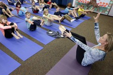 -                FILE - In this Dec. 11, 2012 file photo, Yoga instructor Kristen McCloskey, right, leads a class of third graders at Olivenhain Pioneer Elementary School in Encinitas, Calif. A San Dieg