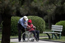 -                In this Thursday, May 23, 2013 photo, an elderly man helps his wife on a wheelchair at a park in Beijing. New wording in the law requiring people to visit or keep in touch with their el