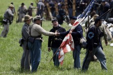 -                Confederate, left, and Union re-enactors meet after a demonstration of Pickett's Charge during ongoing activities commemorating the 150th anniversary of the Battle of Gettysburg, Sunday